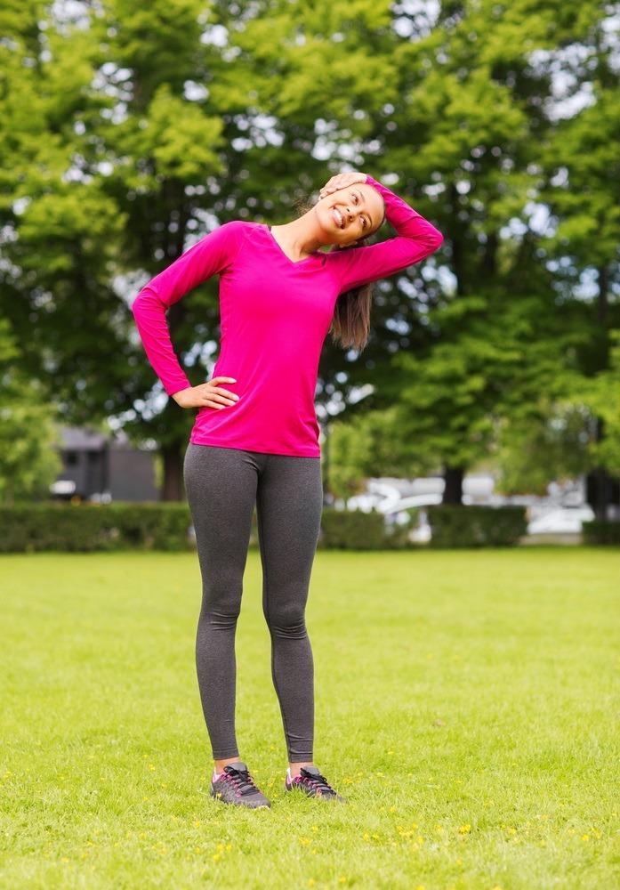 smiling black woman stretching leg outdoors